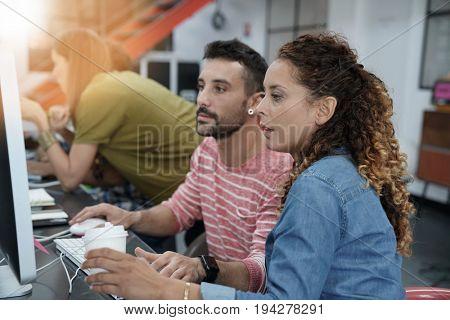 Start-up people working on desktop in co-working space