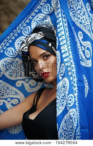 Beautiful oriental woman portrait with red lips and blue oriental veil over her head studio shot