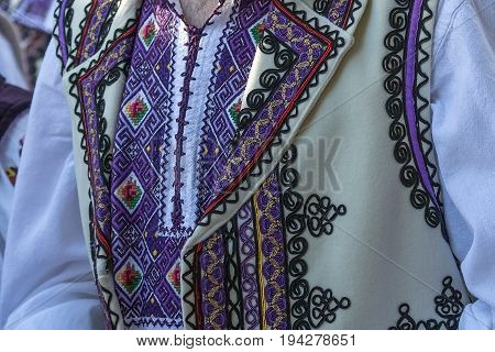 Detail of Romanian folk costume for man with multicolored embroidery.
