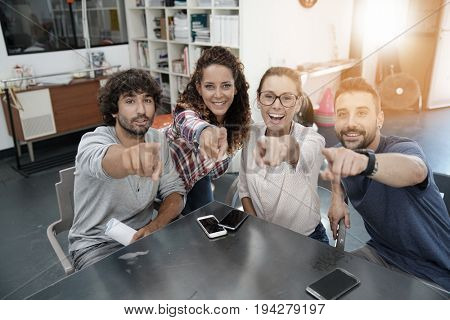 Group of start-up people in office pointing at camera