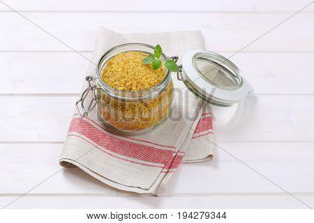 jar of dry wheat bulgur on folded place mat