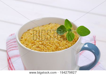 mug of dry wheat bulgur on checkered dishtowel - close up