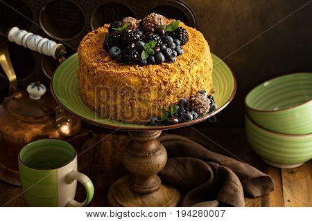 Honey layered cake with crumb topping and fresh berries