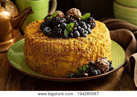 A piece of honey layered cake with crumb topping and fresh berries