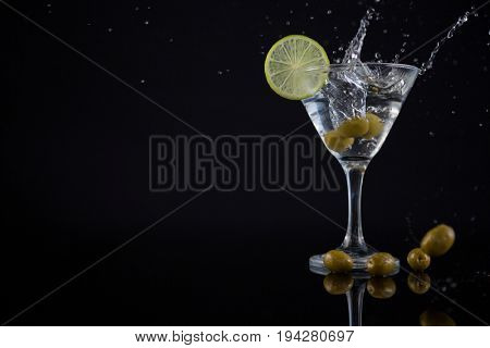 Close-up of olive splashing in to a cocktail martini with lime on table against black background