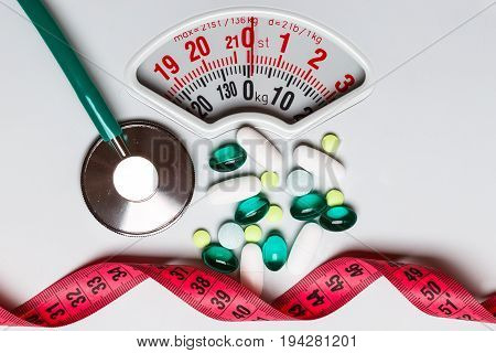 Healthy eating medicine health care food supplements and weight loss concept. Pills with measuring tape and stethoscope on white scales