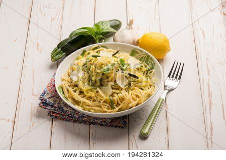 spaghetti with zucchinis parmesan flakes and grated lemon peel