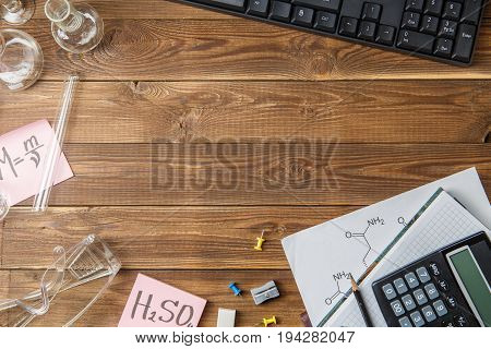 Chemical flasks, tweezers, keyboard, notebooks on a wooden table with copyspase. Educational concept. Top view