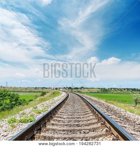 railway to horizon in green landscape under white clouds