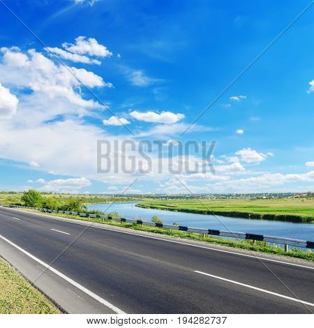 asphalt road and river along it with blue sky over