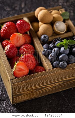 Fresh fruits in wooden box, strawberry, longan and blueberry