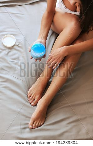 Beautiful woman sitting on bed and applying cream on legs.