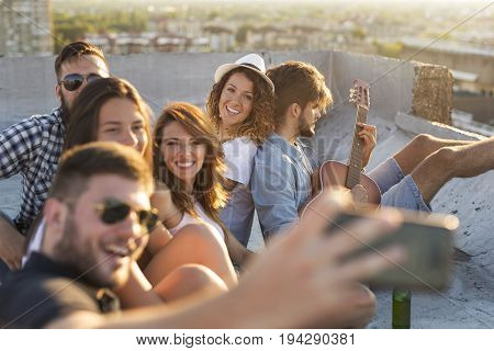 Group of young people playing the guitar singing and having fun at a rooftop party