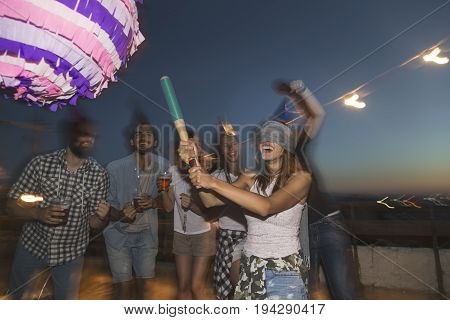 Birthday girl hitting the pinata with baseball bat while her friends are cheering and laughing. Young people having fun at a rooftop birthday party poster