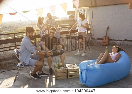 Group of young friends having fun at rooftop party making barbecue drinking beer and enjoying hot summer days. Focus on the man in black T-shirt