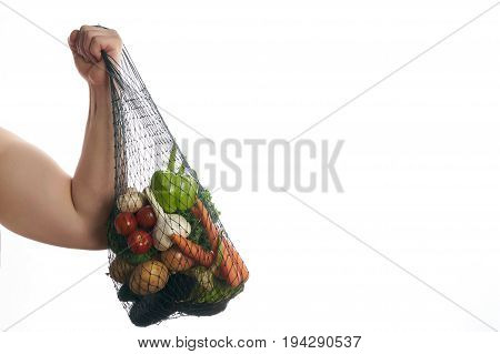 Athlete man flexing his bicep and holding a mesh shopping bag full of vegetables isolated on white background with copy space. Helathy eating and detox concept.