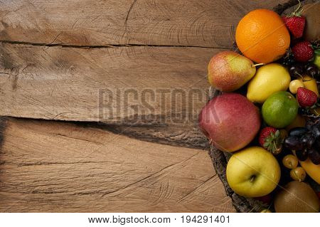 Top view of a fresh raw fruits. Mixed colorful fruits on wooden stump. Healthy eating dieting love fruit. Background with copy space.