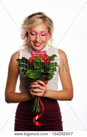 Pretty young teacher with a bouquet of flowers. A gift for the teacher's day. She is wearing a blouse a bow tie and glasses. Back to school.