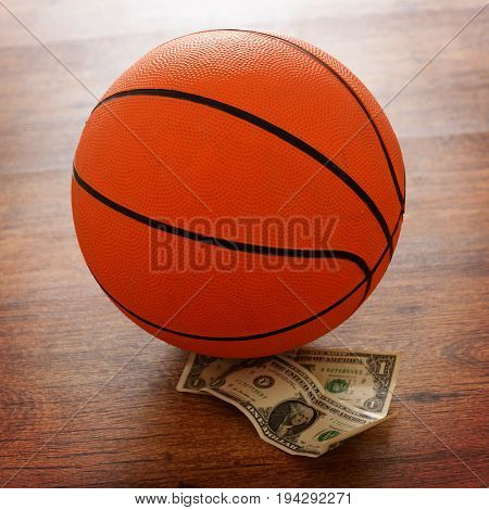 Basketball bet conceptual photo with money and ball on a wooden floor