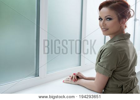 Beautiful brown haired woman in nice khaki jacket and pants posing near the window with a charming smile studio portrait