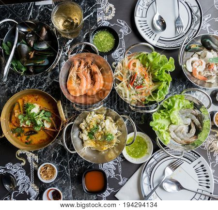 Thai seafood on table Include Tom Yum Goong Papaya salad Oyster Omelette Raw shrimp.