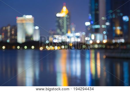 Twilight blurred bokeh light city downtown with reflection abstract background