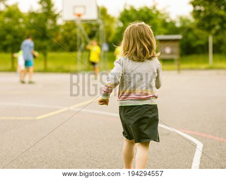 Girl Running Towards Other Boys Playing