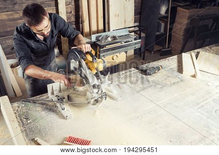 A young male carpenter builder saws a modern circular saw a wooden board in the workshop room