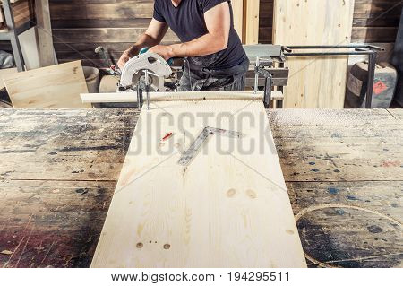 A young male carpenter with a beard and safety glasses saws with a circular saw a wooden board in the workshop