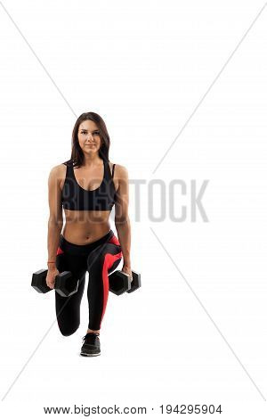 A sporty woman does the lunging of the legs with dumbbells on her biceps legs in full lunge position hands along the torso on a white isolated background