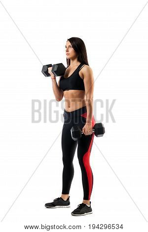 Young athletic woman fitness model doing an exercise with dumbbells on the biceps one arm in a position underneath the second in a bent state on a white isolated background