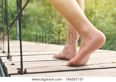 Feet women walking on bridge in nature forest background concept relax time on holiday