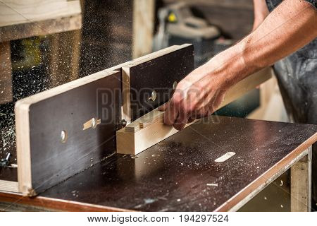 A young male carpenter works wooden at a table in the workshop