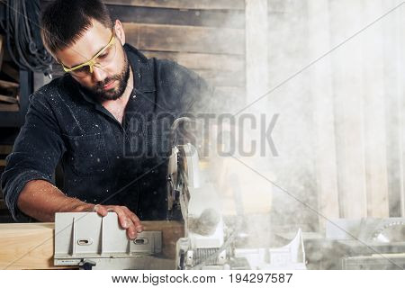 A young man builder sits at a table with tools and saws a wooden board with a circular saw chips fly in different directions in the workshop