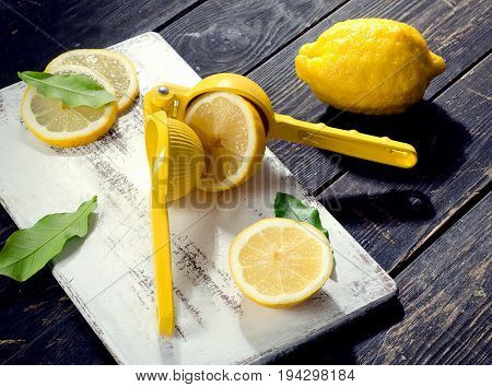 Squeezer And Lemons On  Dark Wooden Board