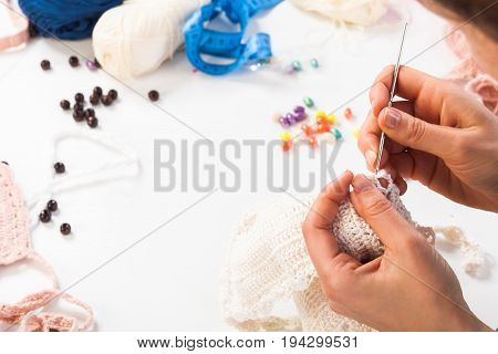 A close-up on top is a table for creativity with knitted things threads beads glasses ribbons. Young woman knits a crochet of white thread scarf