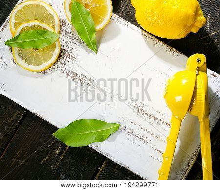 Squeezer And Lemons On A Dark Wooden Board.