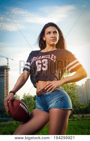 Young athletic girl in short denim shorts and a sports shirt posing against a background in a city park on a sunset background and holding a soccer ball
