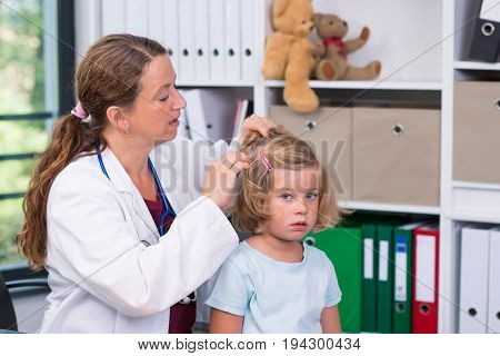 Female Pediatrician In White Lab Coat Examined Little Patient For Lice