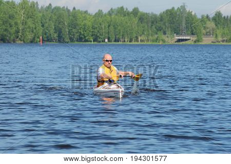 HAMENENLINA, FINLAND - JUNE 10, 2017: A man sails on a kayak on the lake on a sunny June day