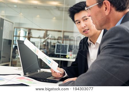 young asian entrepreneur talking to potential investor for his new business