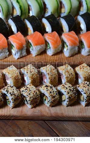 A Macro Shot Of A Sushi Set Of Many Rolls Is Located On A Wooden Cutting Board On A Table In The Kit