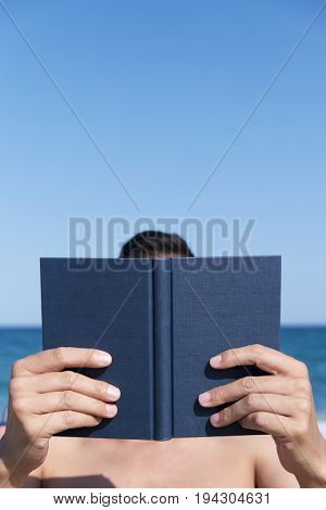 closeup of a young caucasian man reading a book on the beach, with the ocean in the background
