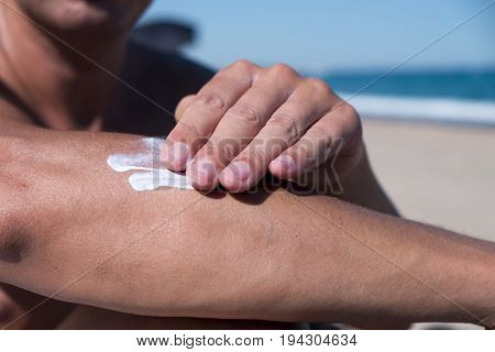 closeup of a young caucasian man on the beach man applying sunscreen to his arm