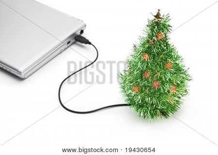 Christmas Vacation. USB Christmas tree connected to a laptop in an empty office. Isolated lighting version. Christmas picture especially for internet related industry.