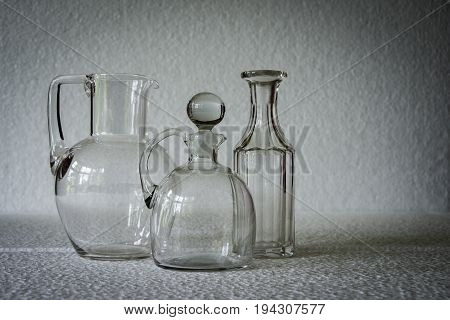 three vintage clear glass liquid receptacles casting a shadow against a white background, with space for overprinting text