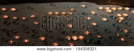 Many small votive candles on a sand in a special holder box in a church
