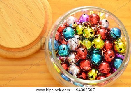 colorful bells in glass bottle and wooden cover on table