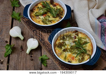 Baked Casserole From Eggs, Bacon, Dried Tomatoes, Broccoli And Cheese In Blue Ramekin On Brown Woode