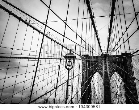 Brooklyn bridge and cable with light pole in black and white